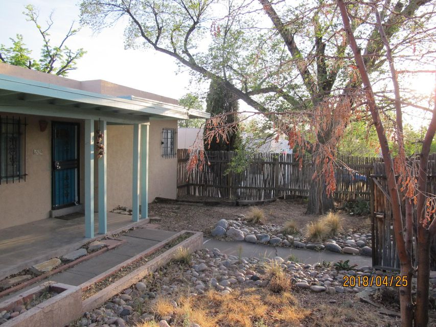 So many reasons to love this home! Close to UNM and Albuquerque's vibrant downtown in an energetic little community. Shady trees behind private coyote fence perfect for porch-sitting while sipping a cold libation. Move-in ready. Enjoy company beside a crackling pinon fire in the living room or behind your closed master bedroom door in front of the traditional kiva fireplace! The master has its own wing and special Picasso-esque tile in its private bath. The kitchen is bright and boasts colorful Talavera tile. Real oak flooring throughout. Garage has a loft for extra storage. Don't wait to be the next lucky owner of this special New Mexican abode!
