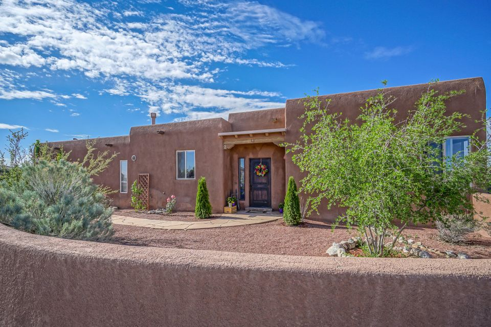 Amazing 360 views from this pueblo style home on 1 acre. Open floor plan with tongue & groove ceilings, vigas, beams & corbels, adobe accent wall, custom wood doors, tile flooring, radiant heat, ceiling fans, cellular shades & alarm system. Kitchen has tile counter tops, breakfast bar, custom cabinetry, pantry, skylights, stainless steel appliances. Spacious master suite with a fabulous view of the Sandia's through a picture window, 2 walk in closets, freshly painted & new carpet, jetted tub & separate shower. 2 bedrooms share a Jack & Jill bath. Large laundry room w/cabinets & counter space. Garage is finished w/insulated door & workshop area. Outdoor living is at its best with a central courtyard with entries from 3 areas of the home. A band of wild horses roams by almost every day.
