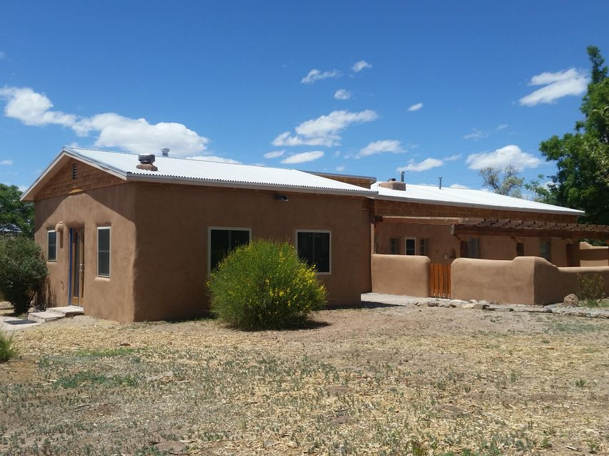 ADOBE in the Village of Placitas! 3 Bdrm, 2.5 Bath on beautiful meadow lot with sweet Sandia views; a tranquil spot with fruit trees & irrigation! 2,070 sq ft with 2 master bdrms, 3rd BR with office, new windows, exposed beams, wood ceilings throughout, saltillo tile, brick & wood floors. Wonderful adobe walls, nichos & plenty of character! Probably built in the 1940s or 50s, the property was used as a Bed & Breakfast for years & the zoning is already in place for a great little B&B! Irrigation ditch along two sides of the property. Enjoy views from the back patio off the master & the huge portal off the great room! Wonderful green location for Placitas! Newer pitched metal roof & brand new septic system. Domestic water is just $30/month & irrigation is only $30/year!