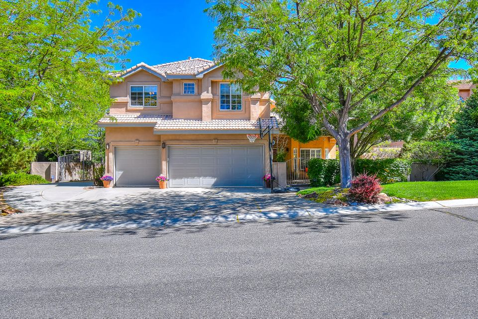 Beautiful 5bd, 3ba home situated on a prestine court lot. The charming courtyard welcomes you into the foyer and formal area w/living and dining rooms. Kitchen with granite counters and island/bar open to nook and family room. One bed downstairs next to the 3/4 ba. Large master suite with desk area, walk-in closet and spacious bathroom. Deck off master showing off the views of the Sandia Mntns. Three addt'l bedrooms upstairs with built-in desk and bookshelves in hall. The backyard is a true retreat with the custom beamed covered patio, built-in grill and fire place. Beautifully manicured front and back yards all on drip. Cinder block shed. Side yard access. NEW PAINT AND CARPET ! Granite counters in all baths. Impeccably cared for -- come see it before it's gone!