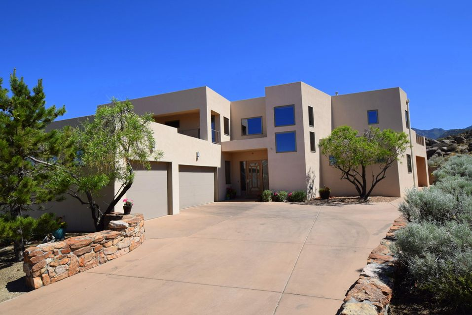 As you enter this magnificent custom home located in the Trailhead at High Desert you are engulfed in breathtaking views of the Sandia Mtns through the 2 story wall of windows**No expense was spared in offering you a seamlessly endless amt of amenities**Great floor plan with luxurious Master Suite on the main level with scrumptious Master Bath and huge walk-in closet**Large additional Master Suites upstairs have their own private baths and balconies**Huge Great Room and Formal Dining Room have two story ceilings and great views of mountains by day and city lights by night**Gourmet Kitchen open to Living Areas has beautiful Cherry Wood Cabinetry, Granite countertops, inviting Service Bar and top of the line Wolf and Sub-Zero stainless steel appliances**Maximum privacy backing to open space