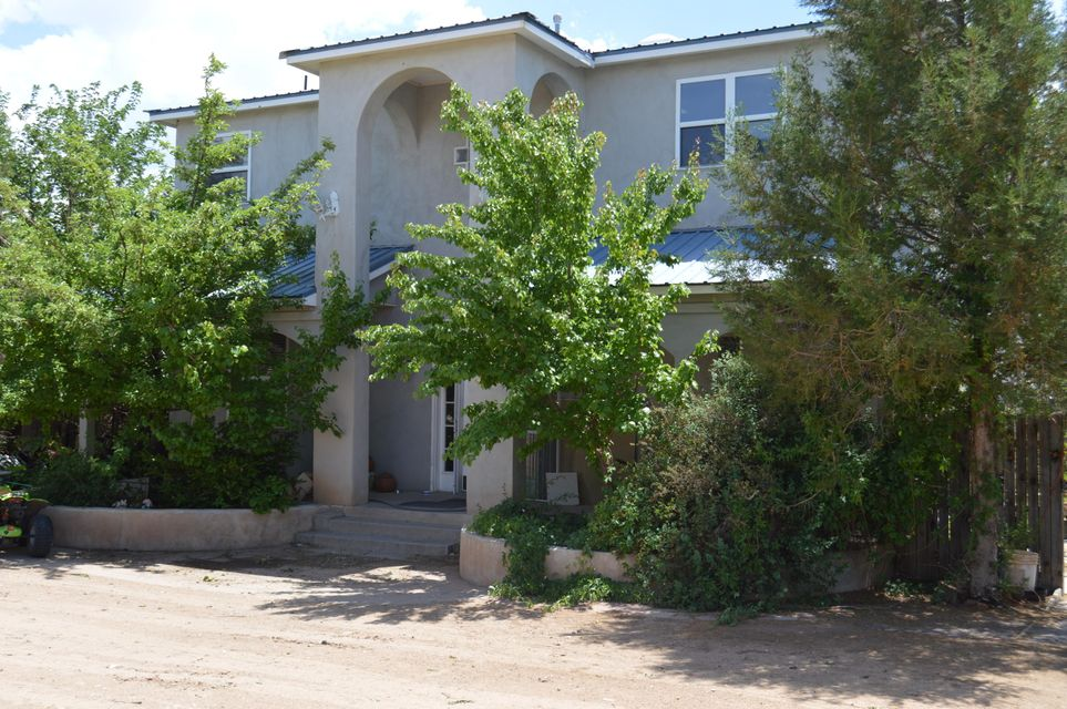 This custom Northern New Mexico style home sits on .87 acre fully fenced. 4 bedroom 3 1/2 bathroom, 2 living areas for entertaining. Large master suite, garden jetted tub, with walk in closet and balcony off master bedroom with great views. Open kitchen, Island with Kitchen Aid stainless steel appliances, separate dining area, ceiling fans, bay windows, lots of storage, Metal Roof.   Large workshop with 3 stall garage