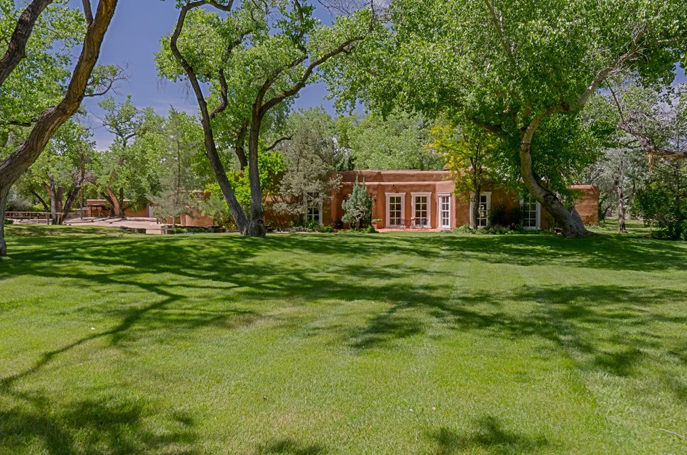 REDUCED PRICE, adjusted acreage & PRICED TO SELL NOW! Stunning PRIVATE adobe sanctuary on a beautiful parcel East of Corrales Rd. Easy access to Rio Grande River, hiking/biking, & Bosque nature trails. Lush pastoral setting on 2.68 acres with stately cottonwoods & palatial landscaping. This Classic home features Gourmet Kitchen, historical windows, formal AND family living & dining, generous bdrms & bths, office, library, Spa like master retreat, 4 fireplaces, 4 car garage, ample RV Parking and swimming pool. Seller in the process of subdividing the lot and any sale is contingent upon approval from the village. Perfect Entertainment Home! This horse property includes barn, tack room, & arena. Detached Guest House is  978 square feet. Home is also available with 1 or 2 additional acres.