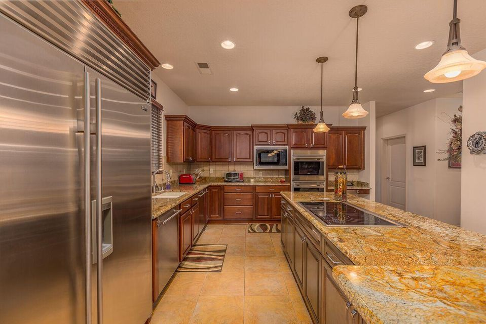 Welcome home to this custom built single story home in a gated area. This property offers a grand entrance with wide doorways and hallways for all stages of life. An entertainers dream kitchen with high end appliances including 2 dishwashers, 2 ovens, 2 pantries and separate wine bar with customer cabinets throughout. The large master offers sitting area to enjoy a nice fire along with jetted tub and separate snail shower with double sinks.  Backyard is fully landscape with just enough grass and beautiful views of Sandia Mountains with a large covered patio to enjoy year round. Oversized garage with 3 cars and RV garage. Includes a 30 amp hook up along with holding tank dump on site. Every part of this house was built with immaculate thought and detail. Do not miss your chance to see thi