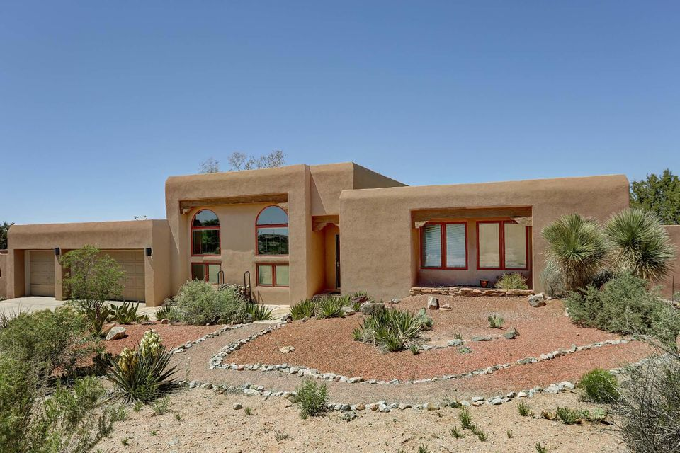 This Spacious SW Contemporary Hacienda w/Wood Ceilings thruout on 2.88 AC has Glorious Views of Sandia & Jemez Mtns, & the Mesas & No Carpeting. This wonderful home has it ALLl! Kt is Open to the LR w/Australian Cyprus Wood Floor, a Dining Area & a Lg Family Room w/Brick Floor & Kiva FP. The Inviting Master Ste includes a Sitting Area, Updated Bath & a Sunroom that also adjoins a second Master Ste adjacent to the Family Room-a perfect In-Law Suite! A Rastra 1372 SF, 2 story Bldg isn't included in SF as it has no built-in heat. It features a Bedroom, Sitting Room & Kitchenette w/MasterCool & wood stove. Downstairs are a Lg Ofc/Studio & Workshop w/sink & stained concrete floors. Outdoor living is unsurpassed w/an inground pool, built-in Hottub & Kiva FP & raised beds for veggies & herbs!