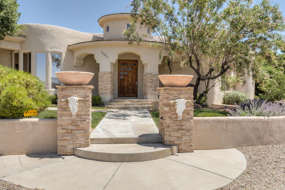 Custom Built- Single Level w/ Contemporary Flair in North Albuquerque Acres! Gourmet kitchen w/ generously sized island, gas cooktop, double ovens, undermount farm sink, under-mount lighting & walk in pantry. Fantastic layout includes the master + office and 3 guest bedrooms + 2 bathrooms on a private wing. Master suite has high ceilings, stacked stone fireplace, airy MBA w/ double sinks, make-up vanity, jetted tub w/separate shower & 200sqft walk-in closet. Fabulous outdoor entertaining w/ outdoor kitchen, large wrap around back patio, covered area w/ outdoor fireplace, in ground gunite pool + hot tub & unobstructed mountain views! HUGE 3 car garage! Located w/ easy access to Paseo Del Norte & Tramway- moments away from trail heads & excellent schools! Schedule your private showing today.