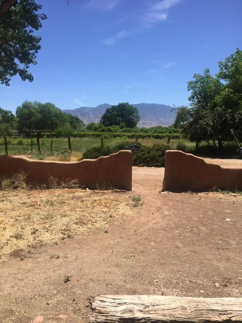 Perfect location in Corrales. Absolutely beautiful views of the Sandia Mountains, the lot is irrigated and has numerous trees. This property includes some horse facilities and a meadow for planting or for grazing. Located just two blocks off of Corrales Road, this home is in the heart of the Village of Corrales. The home has adobe walls, two fireplaces; the one in the master bedroom is a kiva fireplace, brick floors, nichos in the walls and wood ceilings with vigas. With all this beauty the home is a fixer-upper at best but wait until you see the views.