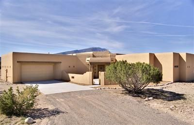 Beautiful custom pueblo style home on 1 acre view lot.  Home was built to maximize stunning views of the Sandias. Custom touches throughout. Large open great room w/tongue & grove ceiling and kiva fireplace. Gourmet kitchen w/custom knotty alder cabinetry, wonderful granite countertops and custom tile work, with raised eat-in bar & large pantry. Zoned radiant heat warms 18 inch floor tile, lighted nichos, skip towel wall textures and custom solid wood doors. Home is on nicely maintained 1 acre lot with plenty of room for your horse.