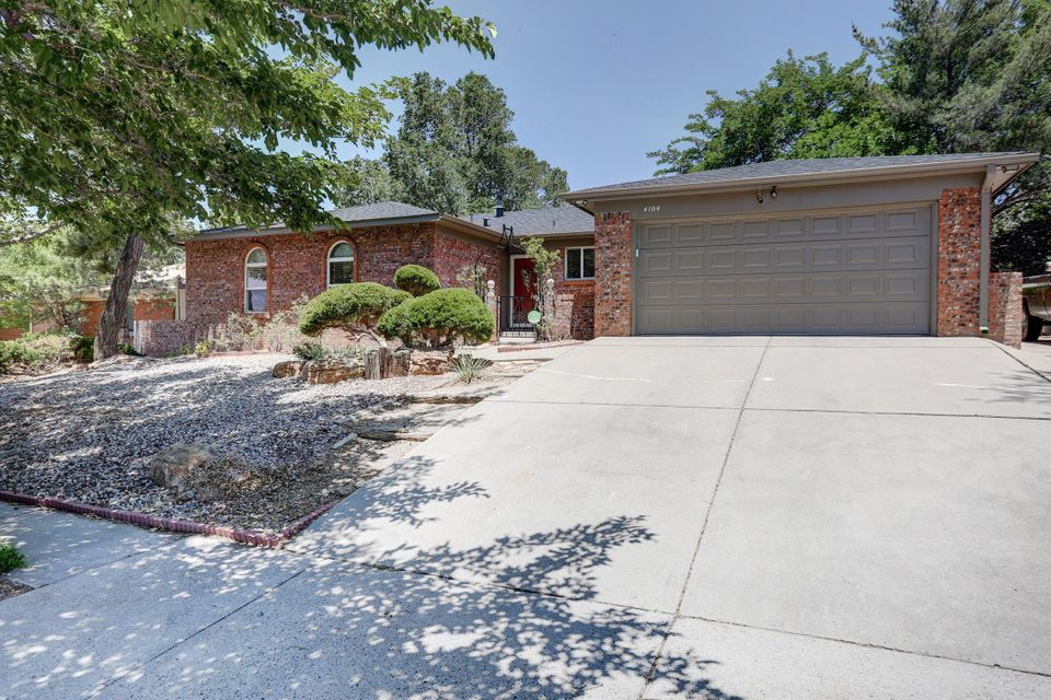 Fantastic Foothills home with NEW ROOF w/ transferable warranty!  So much to love here- updated laminate wood flooring, newer kitchen with stainless appliances newer cabinets and Corian countertops, updated living area w/ gas log fireplace, newer windows, freshly painted exterior trim. FOUR bedrooms, two living areas, 2.5 baths!BONUS nicely finished sun room not included in SQFT! LUSH park like backyard with a storage shed, backyard access, extra parking on the side of the garage. .  Wonderful location offers walking distance to foothills trails.  Easy access to Tramway makes commuting to anywhere life takes you a breeze.