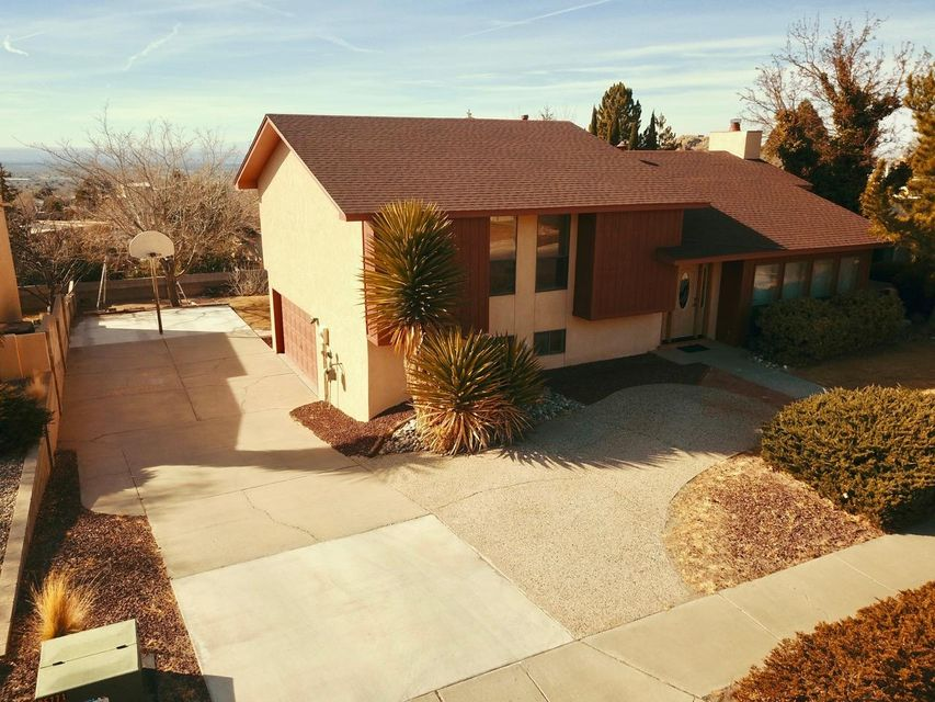OPEN HOUSE - Saturday, June 16th at 10AM! This beautiful home has a great view of the Sandia Mountains and amazing views of the city and sunsets from the upstairs deck and master bedroom! Located just south of the Embudo Hills Park and just north of the Copper Trailhead, this split level home has 3 bedrooms along with a kitchen and dining room upstairs and a living room at ground level. The downstairs has a 4th bedroom/office and an AMAZING 835 SqFt family room and den perfect for entertaining with 2 fireplaces and a wet bar. This foothills jewel has space for an RV/boat and has been well taken care of by the original owners. It has a beautifully updated master bathroom, fresh paint throughout, and new carpet! Other upgrades include stucco (9 yrs), roof (8 yrs), and exterior paint (3 yrs).