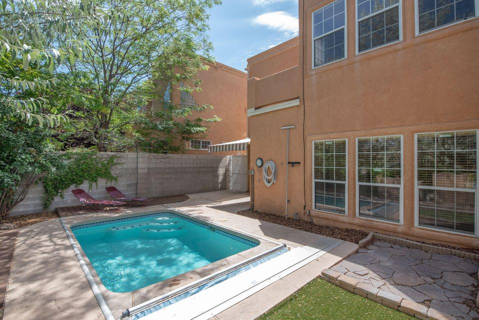 Open House Sunday 9/23.. 1-3 PM Enjoy a gated community with golf courses & more in Tanoan. Light, bright & open 2 story townhome with the MBR down, 2 add'l BRs up, plus a heated sport pool. Soaring living room ceiling defines the architecture of this spacious home. .A care-free yard with no grass to mow, just a sparkling  9' x 14' pool, surrounding deck & an electric awning,(new 6/16)off GR make this a delightful oasis to enjoy. Pool & electric cover are new in the last few years as is the refrigerated AC, new roof (2013), plus heavy duty, secure sliding glass door off the living room. The security system is paid thru the end of 2018. The spacious Master Suite has a walk-in closet, looks over the pool and offers his/her sinks. $5,000 flooring allowance at accepted offer. See more remarks.