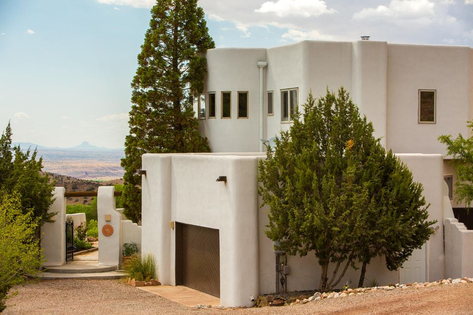 Beautifully crafted custom home offering VIEWS, serenity and tranquility. Carved into the side of the foothills sits an amazing escape boasting tons of natural light and views of Cabezon peak, Rio Grande River Valley and the enchanting Sandias.  Commute to ABQ or Santa Fe. Perfect balance between privacy and convenience. Home was specifically designed for this lot to bring the beautiful outdoors into your daily living. Grand courtyard invites you and your guests into the home where there are 4 entertaining spaces. Rooftop deck is ready for BBQs or quiet outdoor enjoyment. Hot tub on the patio deck?  All bedrooms are upstairs maximizing the privacy and views from each bedroom.  Perfectly Placitas!