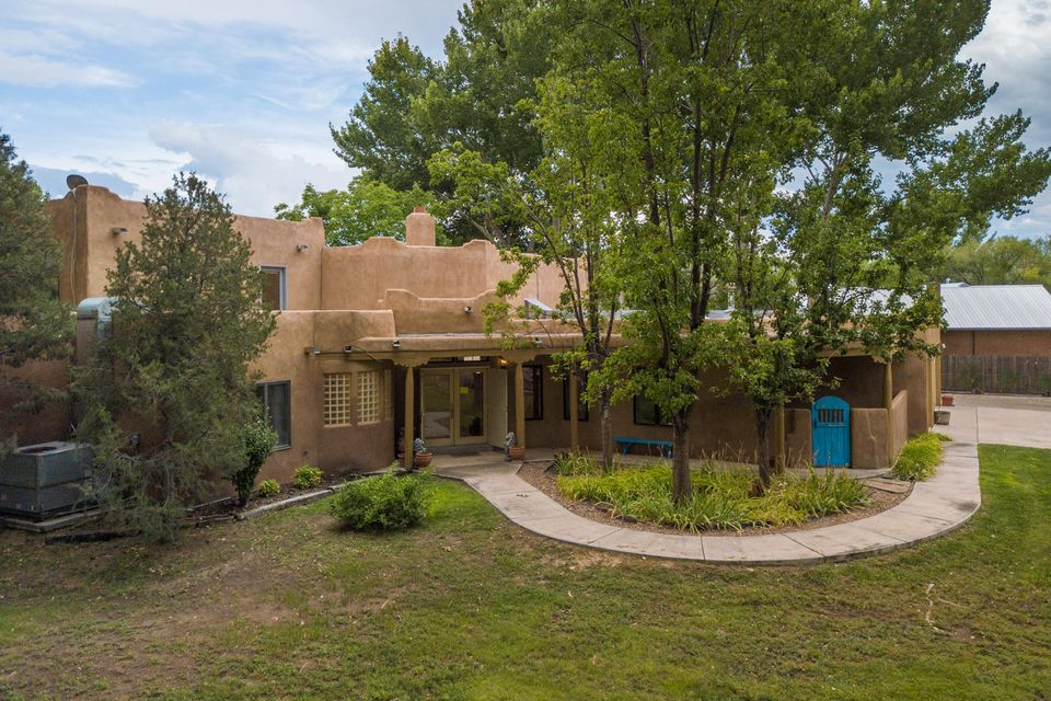 Santa Fe style Pueblo Home w/AMAZING Horse Facilities situated on 2 PREMIUM LOTS on East side of Corrales Rd w/direct access to Bosque trails! Tranquility is yours on this fully fenced & gated, end of culdesac property! Accented w/Southwest designer touches, this home boasts an open & bright floorplan w/custom kiva fireplaces, adobe accents, wood beam Vigas & Korbels, Nichos & Builtins. Indoor heated, Gunite POOL directly off family room can be enjoyed year round. The canopy of trees provide serene outdoor living on the covered portals or open patios. Apprx 1400sqft Horse facilities include 6 stalls, feed & tack rooms, power & water, & riding arena, or exercise your horses along the miles of Bosque next to property. All living areas/bedrooms on one floor, only loft & balcony upstairs.
