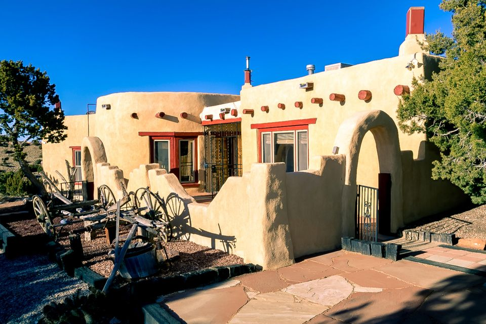 You're invited to see this customized true New Mexico Adobe-style home in the heart of Placitas! Nestled on almost 7 acres of land sits this charming 2800 sq. ft. 3-bed 3-bath home complimented by sprawling natural fields and that Placitas charm. This home is filled with character; featuring over 20,000 Adobe blocks, 20'' thick walls, hand-laid brick flooring, and hand-carved wood doors and Spanish tile all from Guadalajara, Mexico. This home is a true artistic beauty, showcasing custom Southwest designs throughout. You have got to see this property in person! Schedule a private showing and come experience this amazing home.