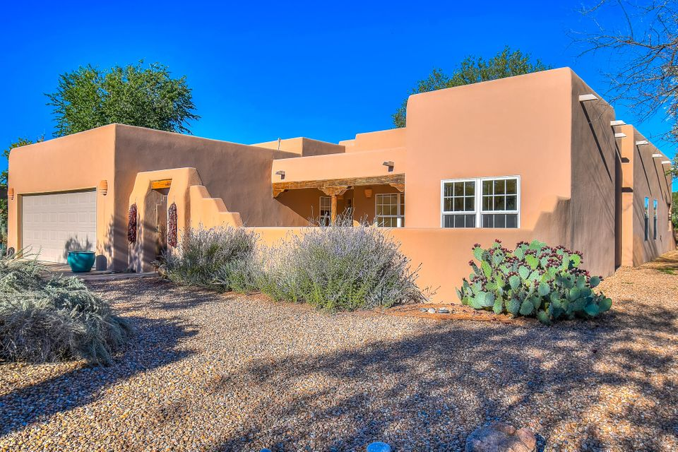 Custom Santa Fe adobe style home in the heart of Corrales. Old world craftsmanship meets modern convenience in this 4 bedroom 2.5 bath one level retreat on .91 acres. Visitors are welcomed by a romantic courtyard. Inside is pure New Mexico: vigas, nichos, adobe walls and wood beams. Step down living room with soaring wood ceilings, tons of light and kiva fireplace. Formal dining room too! Sky lit gourmet kitchen boasts breakfast nook. Large Master Suite with freshly remodeled spa bathroom boasts stone shower and soaking tub. Three more bedrooms share a bath! Fresh carpet and paint. Rooms casually spill onto a spacious covered patio with hot tub and walled courtyard. Yard is bordered by flowers and garden beds. Enjoy the endless sky.