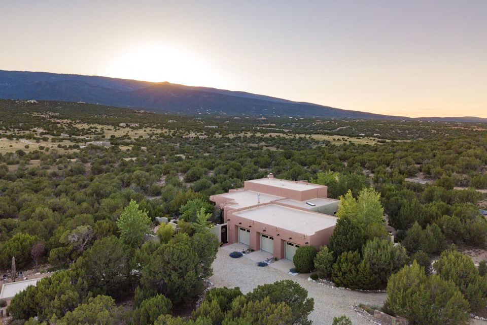 Unbelievable setting on 10 acres with the stunning Sandia Mountain views. Clear views of the Sandia ski runs and golden aspen groves.  Enjoy amazing sunsets while you bask on one of the three outdoor living areas. The home is luxurious in it's own right with soaring ceilings, huge exposed beams, plastered walls and gorgeous tile floors.  Unique owner's suite with dual baths and large closet. You'll love cooking in this kitchen with large island and ample cabinets. 3rd garage bay converted to studio space. Your choice! You'll want to spend a lot of time outdoors with bocce court, spa with views, water features, lovely gardens, a labyrinth for meditation. Horses are welcome with nature trails. New roof in 16,  new stucco in 16, updated septic in 18.  30 min to ABQ, 20 min to Sandia Crest.