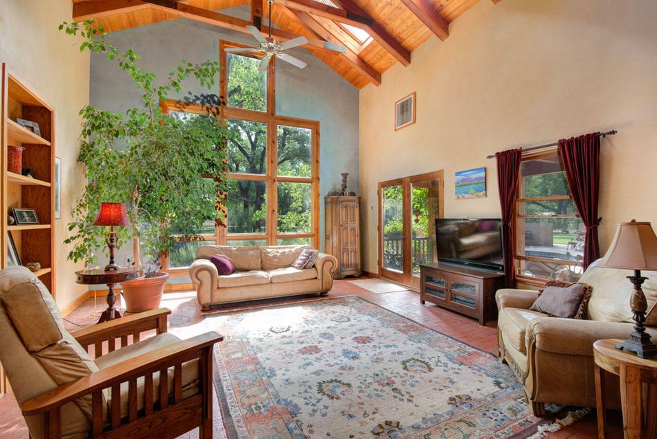 Open House Sunday Oct 14th from 2 to 4. An oasis under a canopy of shade trees with truly amazing in/outdoor living spaces & lush vignettes around a relaxing pool and jacuzzi. Northern NM mini estate features a main house, a separate heated & fully plumbed artist studio, optionally a private 4th family BR or guest house.  Stunning architectural details inside the home are endless! After being greeted by a private front courtyard, you find warm brick floors, plaster walls, & enormous great room with cathedral ceiling. Carved wood tree motifs featured on the front gate, upstairs & 2nd fl patio bannister. Prepare your feasts in a sun-drenched kitchen open to a large dining area & end your day with a walk down to your historical easement off the backyard to the Bosque trail