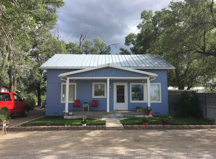 This charming one and a half story house sits on an extra-large lot in town. Home is warm and inviting with lots of handcrafted touches.  The house has two bedrooms downstairs and another two upstairs. Original hardwood floors are through most of the house. All interior water pipes were replaced two years ago. The exterior has new paint, rain gutters, and some new siding. Enjoy the feel of softened water in your shower and washer and drink delicious water from the in-sink RO filter. Fully fenced yard has lots of trees that provide shade. There are also three outbuildings for storage. Sit on the large covered front porch and enjoy the quiet of living in the country!