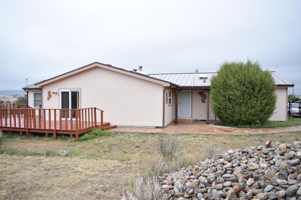 Beautiful country home, at the end of a quiet road, but still only minutes to the freeway. This fenced five acres has a gentle slope, trees, open space, and views of South Mountain and the Sandias. This perfectly kept home has a flexible floor plan - the dining room can be a family room or the great room can have a dining room! However you'd like to arrange it. There is a paneled, heated addition off the master bedroom that could be an office, den, even hold a hot tub! Laminate and tile flooring throughout, and huge closets make for easy living. Outside there is a generous deck off the family/dining room. An oversized garage with an RV space will hold all your toys and hobbies. Fenced and cross fenced for the critters. Come and see!