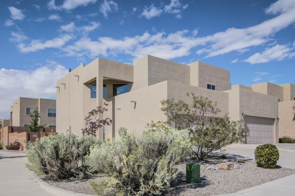 Contemporary-style townhouse in Vista de la Luz! Corner lot end unit gives the feeling of added spaciousness! Main level offers open floorplan with spacious living and dining areas + great kitchen with gas range/oven and pantry. Upstairs is comfortable master bed and bath (double vanity, oversized shower, large walk-in closet), two more bedrooms, full bath and loft. Half-bath powder room and laundry room on main level. Double garage with extra storage. Beautifully xeriscaped yards with auto sprinklers/bubblers  + open patio and extra outside storage. Great Westside location with easy access to I-40 or Montano Bridge via Coors.
