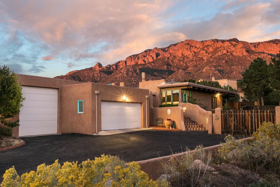 This single level Sandia Heights home sits on a large 1.04 acre lot with stunning views of the Sandia Mountains as well as the city. Enter the home through the private front courtyard in to the light and bright Living Room with a beam/latilla ceiling and a fireplace for the colder winter months. The Kitchen offers a built-in banco seating nook, copper fixtures, and ample cabinet and counter space. The Master Suite offers a large flex space, a wood burning fireplace, his and her closest, and a 3/4 bath. Both secondary bedrooms offer walk-in closets. Private back patio with a built-in BBQ, pot-belly wood stove & horno. Other features include: Tons of storage, a wall-mounted heater in the garage work area, parapet de-icers, a storage shed on concrete, and a garden shed.