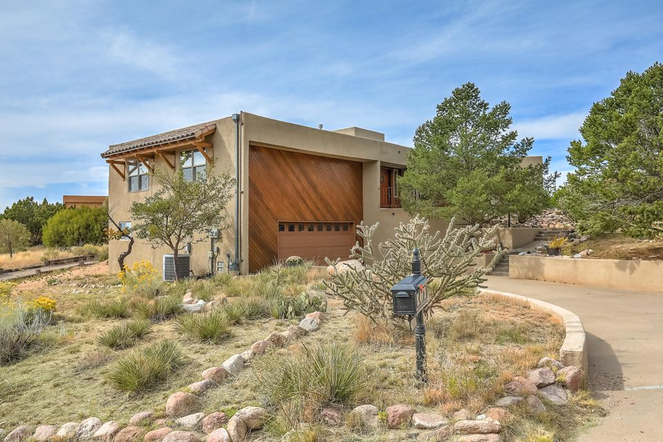 SW style custom home sitting atop a premium elevated view lot at the base of the Sandias just two blocks from the Cibola National Forest.  Incredible mountain to city orientation for spectacular vistas day and night.  Nonstop views plus tremendous natural light.  Major updates since 2001 and meticulously cared for inside and out.  Fantastic kitchen and bathroom revivals, enlarged bedrooms with great storage further add to the functionality of this great custom home.  Chef's kitchen plus private master suite with charming southwest style fireplace plus bonus den/office and hobby room/workshop that is heated and cooled.  Great potential, fantastic location and vistas.  Tremendous opportunity!