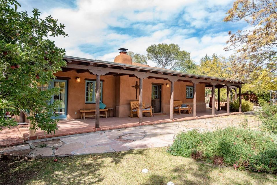 Quintessential North Valley adobe home.  The park like setting welcomes you into this warm and cozy home with brick floors, plaster walls, and a light filled living room. Vigas and 5 kiva fireplaces throughout.  The master suite includes a kiva fireplace, 2 walk in closets, bathroom with jetted tub, separate shower and radiant heat.  Abundant storage including large walk in closets and a mudroom with a wall of cabinets. Oversized 2 car garage plus large storage room.