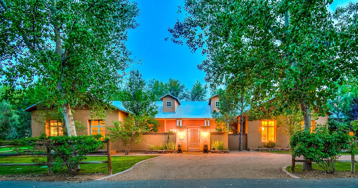 Welcome home to this enchanting North Valley Estate. Single-story custom home located on a coveted private lane amid roses and mature cottonwood trees. This stunning example of Northern New Mexico architecture combines classic charm and modern ease. Open flowing floor plan is perfect for entertaining and showcasing art. Multiple patios invite indoor-outdoor living. Thoughtful floor plan boasts private master suite, separate children's wing and guest wing. Rolling pasture with horse barn. Park like 1.13 acre lot with access to Acequia trails. Secluded, serene and secure yet just minutes to the heart of the city.