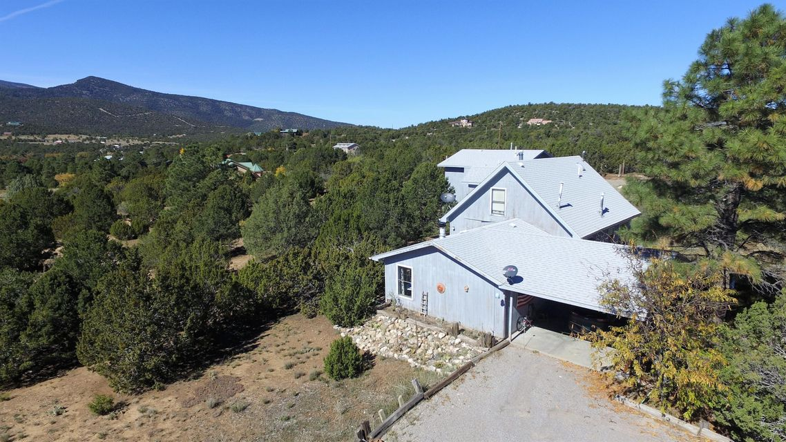 Charming East Mountain home offers privacy and phenomenal views of the Sandia Mountains! Situated on 2 acres this home presents the perfect living situation for those requiring an in-law suite or separate guest quarters. The main house, adorned with natural light throughout, has 3 bedrooms, 2 bathrooms, formal dining room, country style kitchen and 2+ living areas. Additional BONUS is the partially finished basement, which is not included in square footage. The basement, is perfect for a downstairs theater room, game room, storage, oh the possibilities are endless! The upstairs Master Bedroom features pitched ceilings, private wood burning stove, and a generous 14 x 10 walk-in closet.  The detached guesthouse is above the 2-car garage and is complete with its very own kitchen, living room