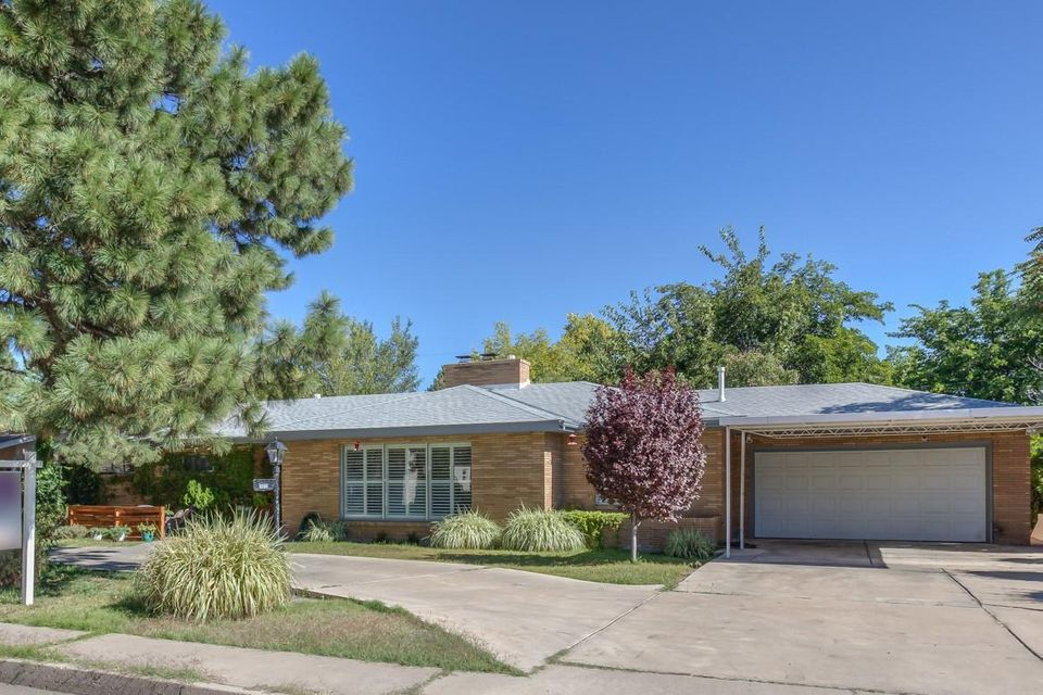 Come entertain in this mid century home, with modern updates sitting on one the largest and private lots in the Albuquerque Country Club neighborhood. Originally built in 1955, this home maintains some of its mid century charm along with plenty of updates including kitchen cabinets and countertops, appliances, plantation shutters/blinds, flooring, raised panel interior doors, and master bathroom updates.   The large and open master bedroom includes a spacious, finished walk in closet and easy access to the fully landscaped private backyard.  Enjoy the cozy gas log and second wood burning fireplaces while waiting for the country club to open up.  Extra storage in your butlers pantry with plenty of additional cabinets.  Enjoy neighborhood benefits being near Zoo, Parks, Old Town, and theater