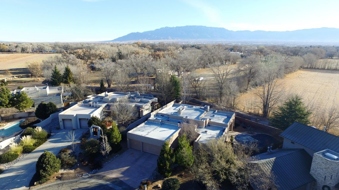 A true gem in Los Poblanos neighborhood in the North Valley. Enjoy this newly renovated home that is nestled in a cul-de-sac that borders the Los Poblano Open Space. Across the fields is the Los Poblanos Historic Inn and Organic Farm and the walking and biking paths along the Bosque Rio Grande. Close and convenient to Old Town, downtown Albuquerque, Los Ranchos de Albuquerque and easy I-40 or I-25 access.This beautiful home boasts newly updated gourmet kitchen with marble countertops, farmhouse style sink and new appliances. Enjoy the newly updated master bath with a deep soaking tub. 3 spacious bedrooms, each with an include bathroom, perfect for privacy. Lovely open floor plan with natural light.  Custom pool to enjoy the hot New Mexico summers with fire pit and two patios.