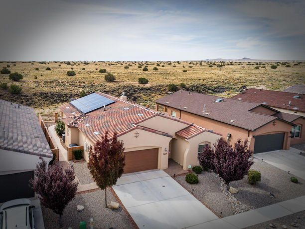 Fall in LOVE with these breath-taking city views, overlooking the Petroglyphs from this beautiful 1702 sq. ft. home. Nestled in a quiet Northwest Neighborhood, this home was built in 2013 and comes with TONS of UPGRADES! Open floor plan with 3 bedrooms, 2 baths, vaulted ceiling, wood and tile flooring, skylights, quartz countertops and comes with all appliances included! Relax and enjoy the beautiful views this home has to offer, with its newer Jacuzzi, or escape in your master bath infrared sauna, all while enjoying the money you save with the Solar Panels that power the home. Entertain with the perfect living space that boast surround sound and gas fire place, or watch the beautiful city skyline during balloon fiesta through the many windows and oversized sliding glass door to the back.