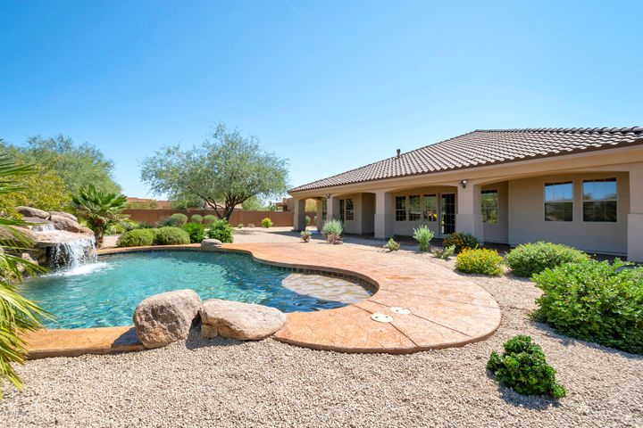 Plenty of shade on the large covered patio to the enjoy the view, pool and rock water feature.