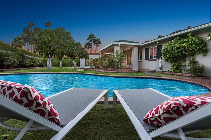 Heated Dive Pool, Lush Grass, and Mature Citrus and Palm Trees in this Fenced in Backyard Resort