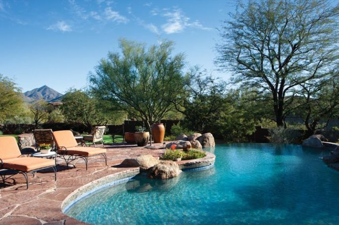 This 5,570sf estate is on 1.1 acres and features lush park-like private grounds anchored by views of the McDowell Mountains.