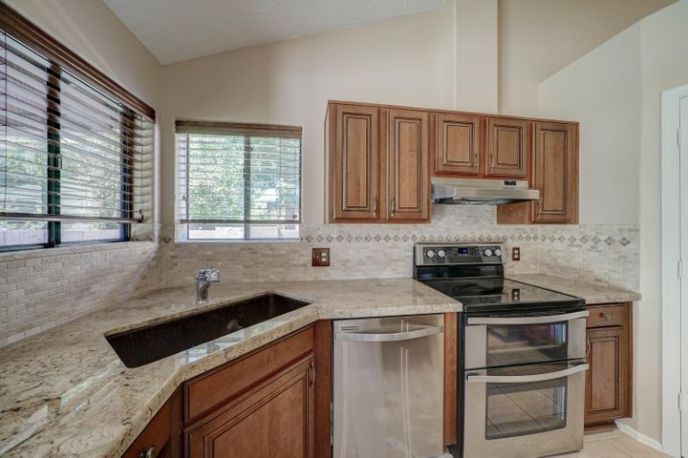 Kitchen with granite counters, matching stainless steel appliances and large pantry.