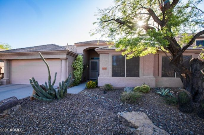 Single story home with easy-care desert landscape in the front yard