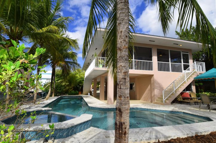 The waterside of the house looks out over the oversized custom pool and spa to the dock with 2 sets of davit & clean flow through canal, perfect for boating and swimming with ocean access.