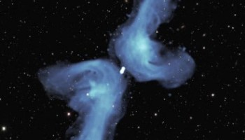 PKS 2014-55 is classified as 'X-shaped' because of its appearance in previous relatively blurry images. The detail provided in this radio image obtained with the MeerKAT telescope indicates that its shape is best described as a double boomerang. Two powerful jets of radio waves, indicated in blue color, each extend 2.5 million light-years into space. Eventually, they are 'turned back' by the pressure of tenuous intergalactic gas. As they flow back towards the central galaxy, they are deflected by its relatively high gas pressure into the shorter, horizontal, arms of the boomerang. The background image shows visible light from myriad galaxies in the distant Universe. Image credit: NRAO / AUI / NSF / SARAO / DES.