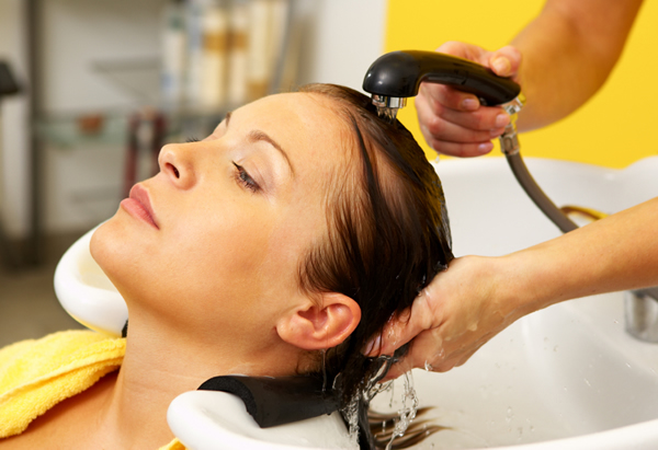 Woman getting hair rinsed at a salon