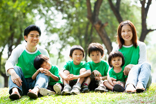 Two parents sit with their four children in a park