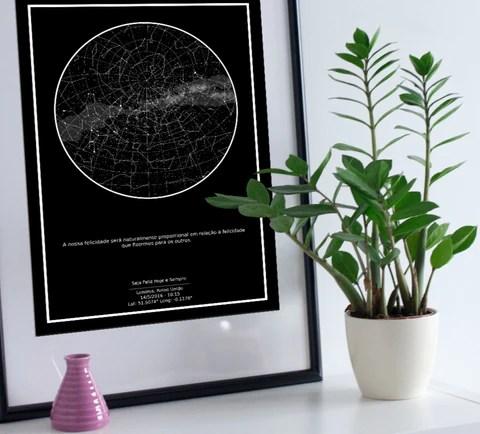 Quadro do Mapa do Meu Céu apoiado em mesa ao lado de uma planta