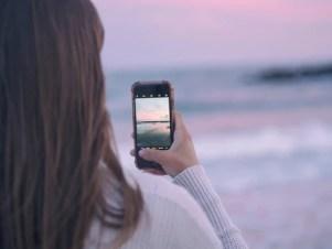imagem de mulher de costas tirando foto de uma paisagem de praia