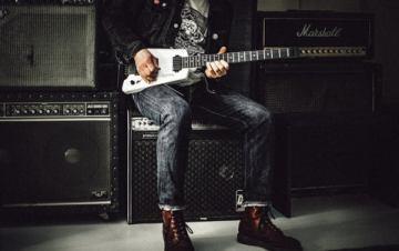 imagem homem tocando guitarra perto de amplificadores