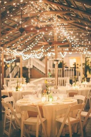 luzes penduradas em teto sob mesas de um casamento. Imagem Pinterest via Paraná Noivas