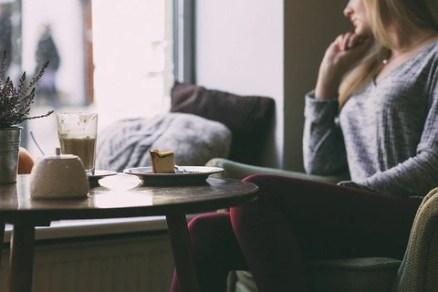 mulher sentada em sofá observa a janela pensativa