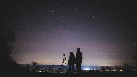 silhueta de casal observando as estrelas