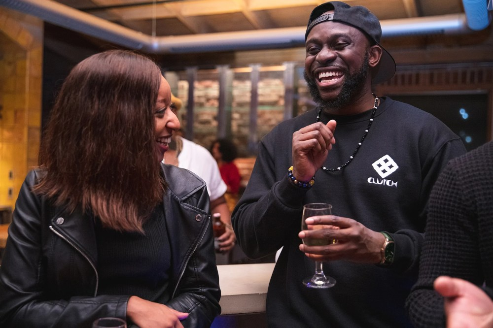 A woman in a leather jacket laughs with a man holding a wine glass at an event at AfroTech 2019.
