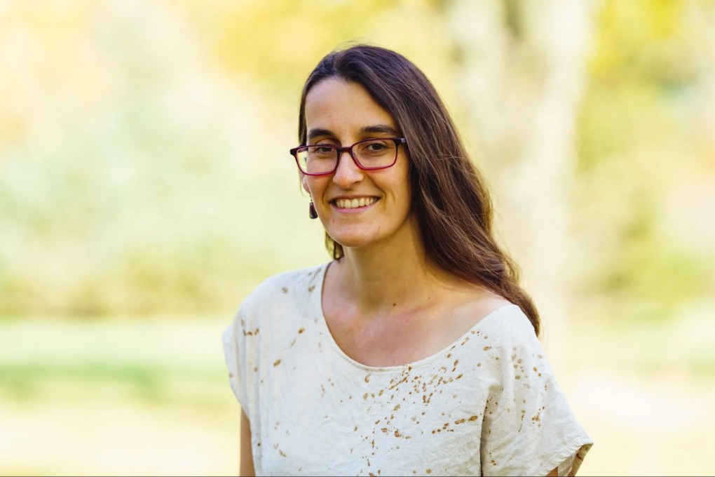 Sarah Resnick the creator and owner of Gist Yarn in a white shirt with gold speckles against a green outdoorsy background.