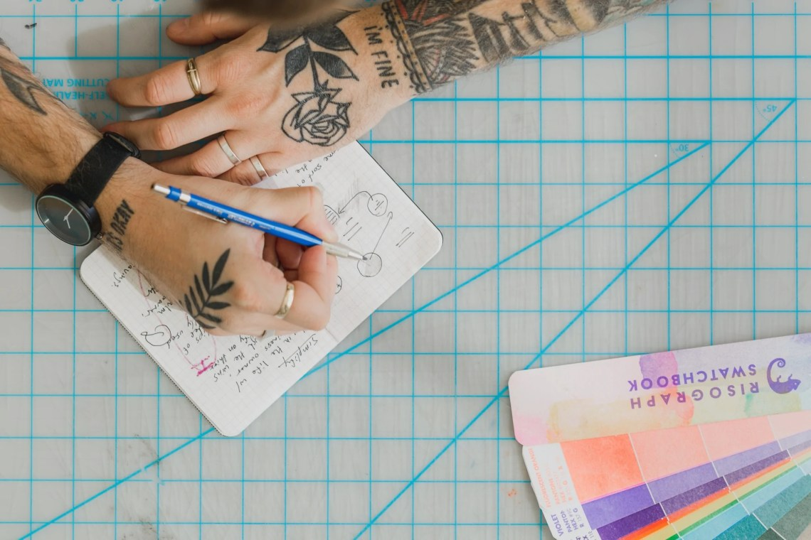 Close up of tattooed hands writing in a notebook
